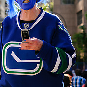 Vancouver, British Columbia, Canada - June 6, 2011 - A fan walks down the street to gather with the crowd and watch a Stanley Cup Playoff game (Vancouver 1-8 Boston) outdoors courtesy of the CBC.<br /> <br /> Image: © Rod Mountain<br /> <br /> http://www.rodmountain.com<br /> <br /> Nikon D800 / Nikkor Lens<br /> @nikoncanada #NikonCA<br /> @NikonUSA #NikonNoFilter<br /> @nikoneurope #NikonEurope<br /> <br /> https://en.m.wikipedia.org/wiki/Vancouver_Canucks<br /> <br /> #VancouverCanada #hockeylife #hockeyfan #2011 #vancouver #gametime #hockey #vancouvercanucks #playoffs #sport #fans #playoffgame #cbc #latergram
