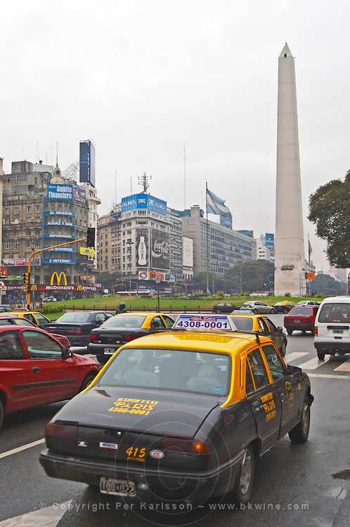 The obelisk, obelisco, on the Plaza de la Republica Square on the Avenida 9 Julio Avenue of ninth of July, taxis and cars in the foreground. Traffic. Modern office buildings. Buenos Aires Argentina, South America