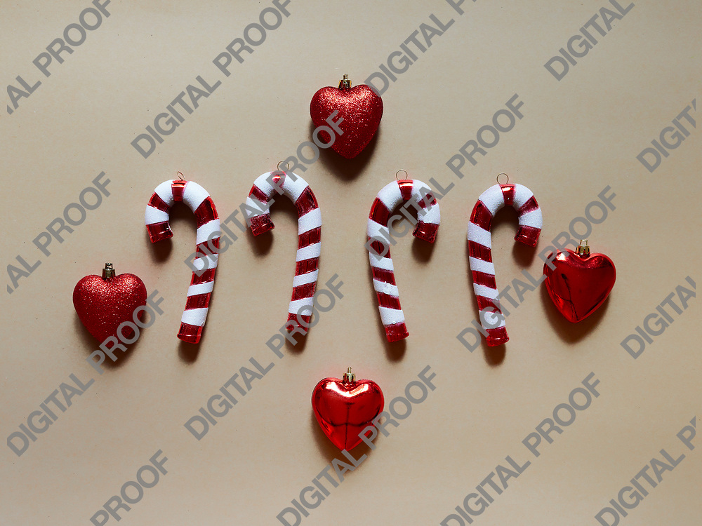 Christmas candy cane and hearts at studio above view over a brown background isolated flatlay