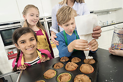 Schoolboy icing on muffins with icing bag in home economics class, Bavaria, Germany