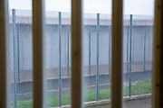 A view through bars and two security fences of the exterior wall outside from a cell window at HMP Bronzefield, a private prison run by Sodexo Justice Services on the outskirts of Ashford in Middlesex, United Kingdom. HMP Bronzefield is an adult and young offender female prison, the only purpose built private prison solely for women in the UK and is the largest female prison in Europe. (photo by Andy Aitchison)