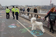 Police officers and Climate Change graffiti from Extinction Rebellion campaign for a better future for planet Earth after blocking Waterloo Bridge and as part of a multi-location 5-day Easter protest around the capital, on 16th April 2019, in London, England.