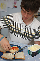 Teenager making sandwiches