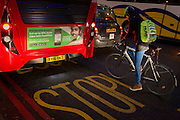 A cyclist pauses behind a bus featuring the Farepilot app in winter traffic on Bishopsgate, on 9th February 2017, in the City of London, England.