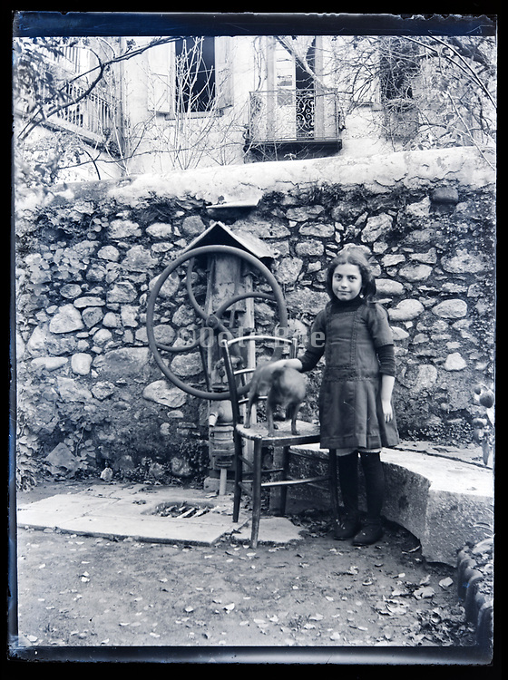 little girl with pet dog standing by the outdoors water pump France circa 1920s