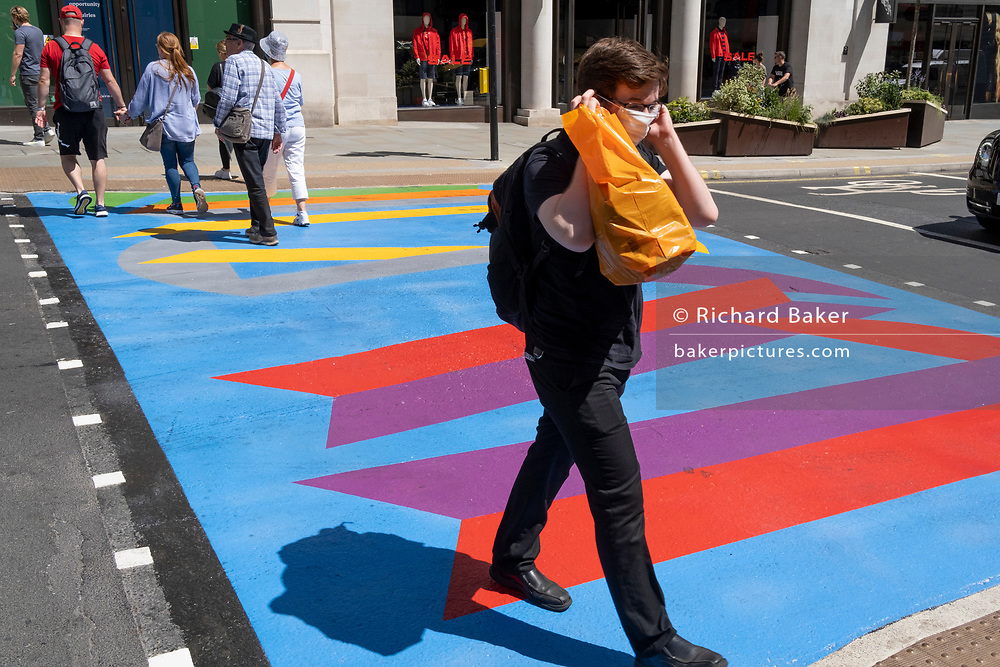 A man adjusts his face covering as he walks over the multi-coloured markings of a crossing at Lower Regent Street, on 16th July 2021, in London, England.