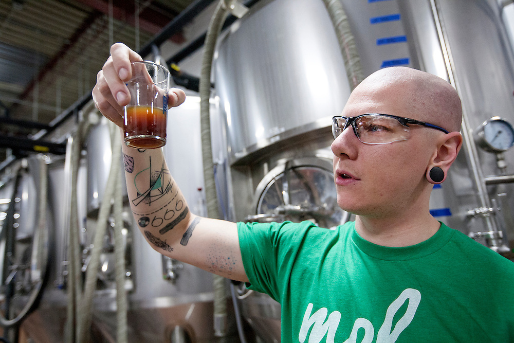 Lee Carter, one of 5 founders of Big Watt Cold Beverage Co., checks a cold press coffee sample that has one remaining filtration cycle left at Burning Brothers Brewing in St. Paul December 15, 2015.  After much trial and error, Big Watt has created a process by which it is able to can coffee free of preservatives that is shelf stable for 16 months without cold storage.