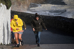 © London News Pictures. 16/10/2017. Portleven, UK. Members of the public shelter form wind and rain as Huge waves batter the coastline at Portleven in Cornwall as the remnants of storm system Ophelia reaches the UK. The Met Office has issued an Amber weather warning, with a good chance that power cuts may occur, with the potential to affect other services, such as mobile phone coverage.. Photo credit: Mark Hemsworth/LNP