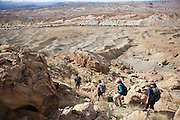 Students, on a geology field trip with the University of Colorado, descend the steep trail that provides access to the rim of North Caineville Mesa, Utah.