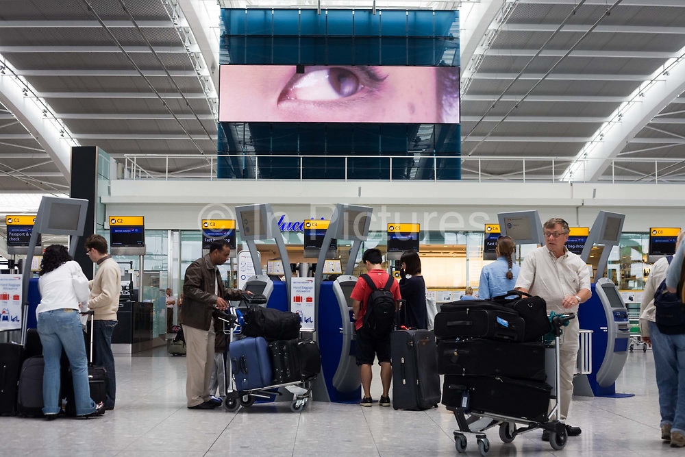 """A scene of busy modern air travel as international passengers check-in at the British Airways Heathrow Airport's Terminal 5. Under the gaze of a giant eye that seems to be peering from out of a massive TV screen, the self-service kiosks that have been developed to allow customers to process their own ticketing on arrival at this aviation hub for British Airways. Once they've chosen their seat and printed a boarding pass, they can go straight to the Fast Bag Drop desk at the airport. There, baggage will be tagged by an agent and sent to the aircraft. At a cost of £4.3 billion, Terminal 5 has the capacity to serve around 30 million passengers a year. From writer Alain de Botton's book project """"A Week at the Airport: A Heathrow Diary"""" (2009). ..."""