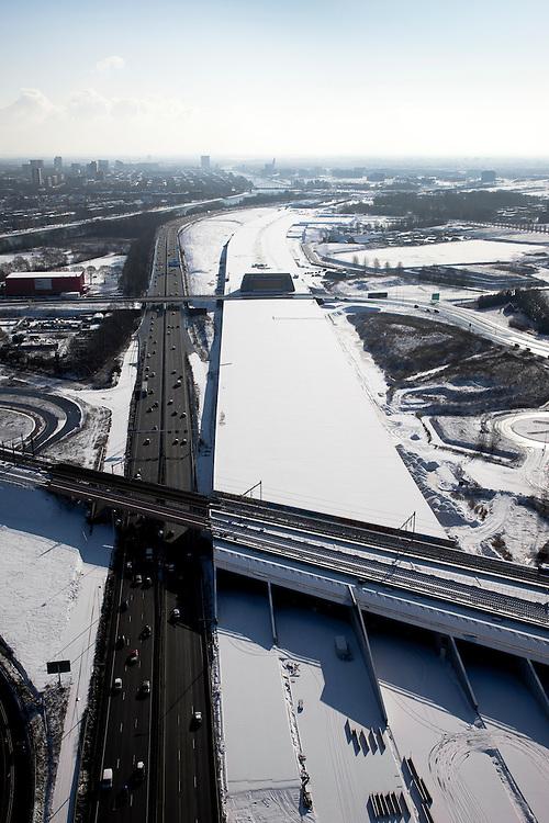 Nederland, Utrecht, Leidsche Rijn, 31-01-2010; de ingang van de nieuwe landtunnel voor de A2, met vier tunnelbuizen. De tunnel ligt parallel aan de bestaande A2, het asfalt zal op termijn verdwijnen. Op het dak van de tunnel zal een park komen. Links het Amsterdam-Rijnkanaal, skyline Utrecht aan de horizon. De verbreedde spoorlijn Utrecht-Gouda gaat over de ingang tunnelbuizen..Entrance of the new landtunnel for A2, with four tunnel tubes. The tunnel lies parallel to the existing A2, the asphalt will eventually disappear. The roof of the tunnel will be a park. Left the Amsterdam-Rhine Canal, Utrecht skyline on the horizon. The broadened railway line Utrecht-Gouda above the entrance tunnel tubes (foreground).luchtfoto (toeslag), aerial photo (additional fee required).foto/photo Siebe Swart