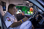 """Oct. 1, 2009 -- BANGKOK, THAILAND:  ORACHUN, a medic and shift supervisor with Poh Teck Tung, does paperwork in his ambulance between calls. The 1,000 plus volunteers of the Poh Teck Tung Foundation are really Bangkok's first responders. Famous because they pick up the dead bodies after murders, traffic accidents, suicides and other unplanned, often violent deaths, they really do much more. Their medics respond to medical emergencies, from minor bumps and scrapes to major trauma. Their technicians respond to building collapses and traffic accidents with heavy equipment and the """"Jaws of Life"""" and their divers respond to accidents in the rivers and khlongs of Bangkok. The organization was founded by Chinese immigrants in Bangkok in 1909. Their efforts include a hospital, college tuition for the poor and tsunami relief.    Photo by Jack Kurtz / ZUMA Press"""