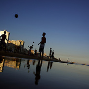Locals practice with footballs during the late afternoon sun on Ipanema beach, Rio de Janeiro,  Brazil. 6th July 2010. Photo Tim Clayton..
