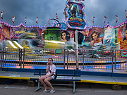14 AUGUST 2019 - DES MOINES, IOWA: A girl sits in front of the Magnum ride at the Iowa State Fair. The Iowa State Fair is one of the largest state fairs in the U.S. More than one million people usually visit the fair during its ten day run. The 2019 fair run from August 8 to 18.                PHOTO BY JACK KURTZ
