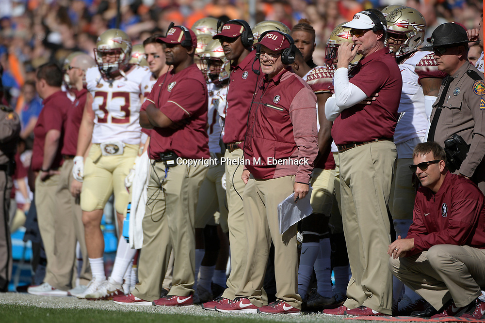 Florida State head coach Jimbo Fisher, center, and his coaching staff watch from the sideline during the second half of an NCAA college football game against Florida Saturday, Nov. 25, 2017, in Gainesville, Fla. FSU won 38-22. (Photo by Phelan M. Ebenhack)