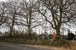 Great Missenden, UK. 9th April, 2021. A HS2 security contractor guards a fenced area on Leather Lane where several hundred-year-old oak trees have been felled to enable the construction of a temporary access road and compound for the HS2 high-speed rail link. Following pressure from local residents (over 40,000 people signed a petition to save the trees), Buckinghamshire Council and the Chilterns Conservation Board, it appears that HS2's plans have been changed in such a way as to preserve some of the trees along the wildlife-rich ancient country lane.