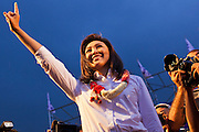 01 JULY 2011 - BANGKOK, THAILAND:  YINGLUCK SHINAWATRA, leader of the Pheua Thai party, greets voters at the last Pheua Thai rally of the year in Bangkok Friday. Thailand's divisive election campaign drew to a close Friday in Bangkok. Most of the parties had large rallies in an effort to sway last minute undecided voters. Pheua Thai, the party of ousted Prime Minister Thaksin Shinawatra held a massive rally in Rajamakala Stadium (also called Ramkamhaeng Stadium) to close out their campaign. A monsoon thunderstorm didn't keep people away from the event. Most Thai public opinion polls show Pheua Thai with a healthy lead over their arch rivals (and incumbent party in power) the Democrats. Thaksin's youngest sister, Yingluck Shinawatra, is running for Prime Minister under the Pheua Thai banner. If elected, she will be Thailand's first female Prime Minister.      PHOTO BY JACK KURTZ