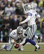 Dallas Cowboys' Tony Romo bobbles the snap as kicker Martin Gramatica steps in for the kick with 1:09 left in the game against Seattle Seahawks in an NFC wild-card playoff football in Seattle, Saturday, Jan. 6, 2007. Romo attempted to run the ball but fumbled as he was hit. The Seahawks won 21-20. (AP Photo/John Froschauer)