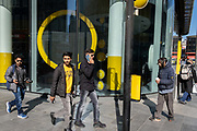 The yellow theme shapes and window design of confectionary retailer M&Ms, with passers-by during the third lockdown of the Coronavirus pandemic, on 29th March 2021, in London, England.