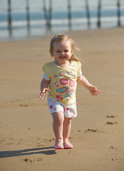 © Licensed to London News Pictures. 28/03/2012..Saltburn, England..As temperatures rise this week the beach at Saltburn in Cleveland attracts the visitors as they enjoy the warm weather. Polly Wells, 18 months, from Middlesbrough enjoys a run on the sand...Photo credit : Ian Forsyth/LNP