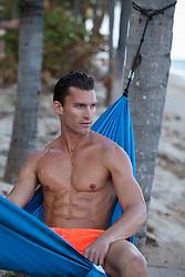 hot man in a hammock at the ocean