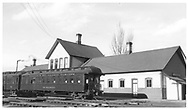 """D&RGW parlor car """"Durango"""" in front of Durango depot which has chimneys.  """"San Juan cars waiting to be turned.""""<br /> D&RGW  Durango, CO  Taken by Maxwell, John W. - 2/28/1946"""