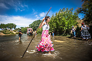 """A young girl recently baptized in the river, walk crossing over """"Vado del Quema"""" as the cart of their brotherhood starts it."""