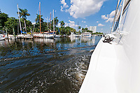 Yacht navigating the Miami river with view of marinas