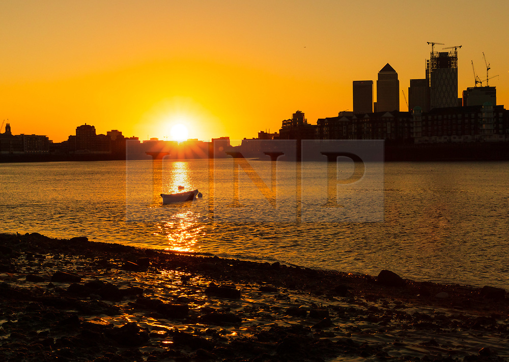 © Licensed to London News Pictures. 07/09/2018. London, UK.  Sunrise at low tide on the River Thames this morning, seen behind the Canary Wharf financial district. Photo credit: Vickie Flores/LNP