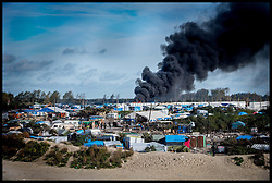 October 27, 2016 - Calais, Northern France, France - Calais Jungle Migrant Camp. Fires still burning among the remains of  the migrant camp as Refugees leave the Calais Jungle migrant camp the day after it caught fire and the French police closed it down. (Credit Image: © Andrew Parsons/i-Images via ZUMA Wire)