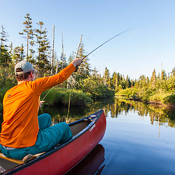 """A man fly-fishing for brook trout from a canoe on the Cold Stream """"deadwater"""" above Upper Cold Stream Falls in Maine's Northern Forest. Johnson Mountain Township."""