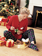 Jane is opening up her Christmas gifts in front of a trimmed tree, while modeling her flannel fashion for Charles Keath.