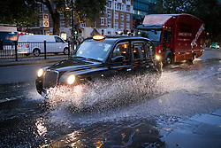 © Licensed to London News Pictures. 21/10/2021. London, UK. A taxi drives through surface water on the Euston road in North London caused by heavy rain over night in the capital. Flash flooding hit parts of the south east as Storm Aurore brought winds of up to 45mph . Photo credit: Ben Cawthra/LNP
