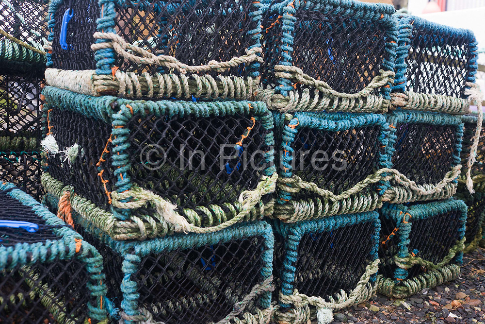 Stacked fishing Creels are stacked on the quayside at Fionnphort pier head, Isle of Mull, Scotland. The creel is a type of small wicker basket mainly used by anglers to hold fish or other prey. A creel is designed to function as an evaporative cooler when lined with moss and dipped into the creek in order to keep the catch chilled. Caught fish are inserted through a slot in the top which is held in place by a small leather strap.