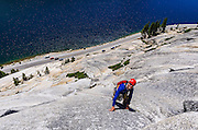 Rock climber on Stately Pleasure Dome above Tenaya lake, Tuolumne Meadows, Yosemite National Park, California USA