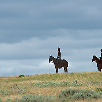 Silhouetted steel ranchers ride across the priaires of Phllips County, Montana.