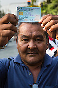 """01 FEBRUARY 2014 - BANGKOK, THAILAND:  A Thai voter holds his national ID card over his head to a march to a polling place to vote. The voters were turned back by police who blocked access to the polls because armed anti-government protestors would not allow voters to cast their ballots. Thais went to the polls in a """"snap election"""" Sunday called in December after Prime Minister Yingluck Shinawatra dissolved the parliament in the face of large anti-government protests in Bangkok. The anti-government opposition, led by the People's Democratic Reform Committee (PDRC), called for a boycott of the election and threatened to disrupt voting. Many polling places in Bangkok were closed by protestors who blocked access to the polls or distribution of ballots. The result of the election are likely to be contested in the Thai Constitutional Court and may be invalidated because there won't be quorum in the Thai parliament.   PHOTO BY JACK KURTZ"""