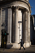 A City man walks past beneath the tall Corinthian-style columns of the Bank of England on the corner of Princes Street and Threadneedle Street EC2, at two entrances of Bank Underground station, on 22nd January 2019, in London England.