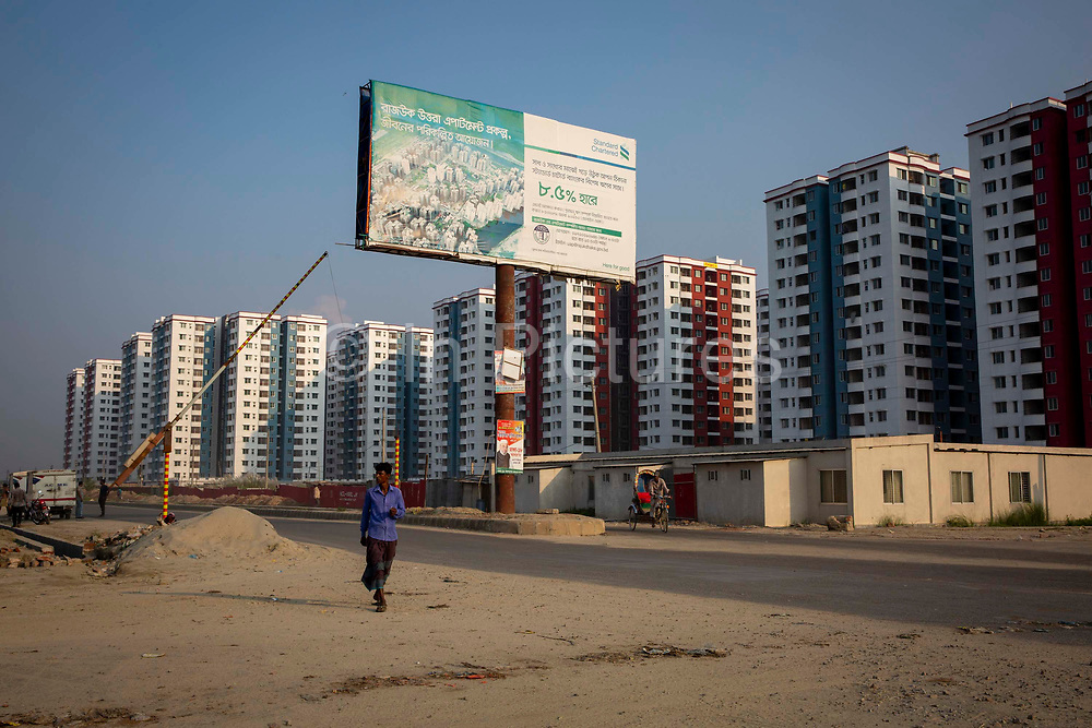 An advertising board for bank finance outisde the high rise blocks of Rajuk Uttara Apartment Project in section 16 of Uttara residential model town district on the 30th of September 2018 in Dhaka, Bangladesh. Agricultural land is slowly being taken over in the districts around Dhaka for housing development.