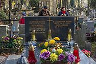 A family visits a grave at Rakowicki cemetery in Krakow, Poland 2019.
