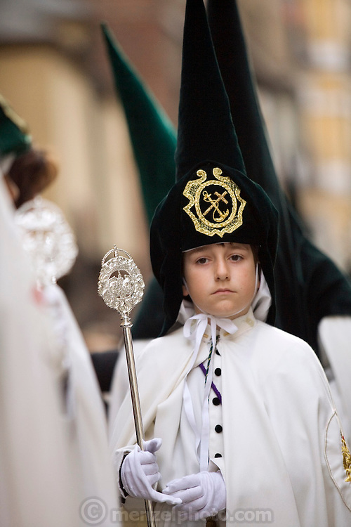 A young hooded penitent in a procession during Holy week in Salamanca, Spain. Street processions are organized in most Spanish towns each evening, from Palm Sunday to Easter Sunday. People carry statues of saints on floats or wooden platforms, and an atmosphere of mourning can seem quite oppressive to onlookers.