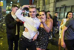 """© Licensed to London News Pictures . 23/12/2017. Manchester, UK. A man wearing a crown walks with a woman along Withy Grove , outside the Printworks . Revellers out in Manchester City Centre overnight during """" Mad Friday """" , named for being one of the busiest nights of the year for the emergency services in the UK . Photo credit: Joel Goodman/LNP"""