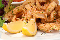 Macro of lemons and fried calamari, use of selective focus, plenty of copyspace.