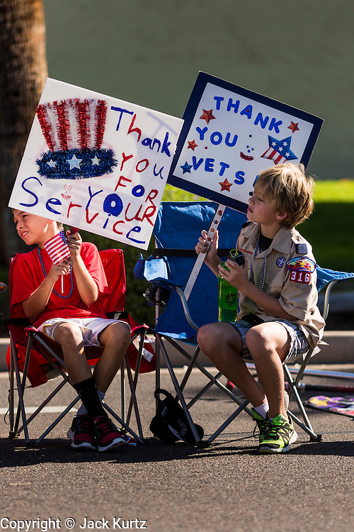 """11 NOVEMBER 2013 - PHOENIX, AZ: Boy Scouts cheer passing veterans at the Phoenix Veterans Day Parade. The Phoenix Veterans Day Parade is one of the largest in the United States. Thousands of people line the 3.5 mile parade route and more than 85 units participate in the parade. The theme of this year's parade is """"saluting America's veterans.""""    PHOTO BY JACK KURTZ"""