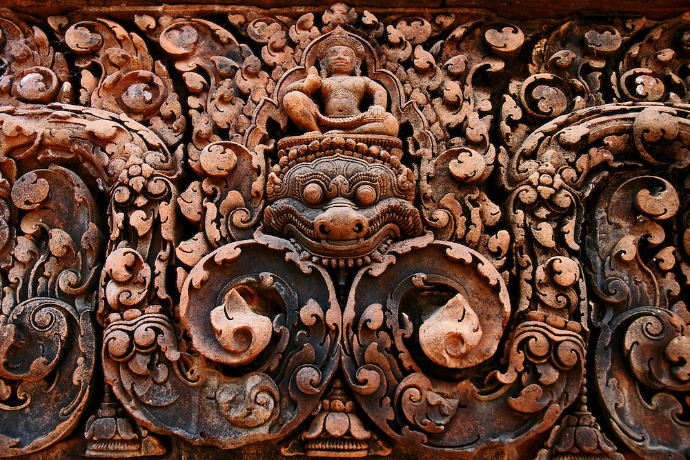 This ornamental bas-relief of a kala is from Banteay Srei, a richly decorated, late 10th century Hindu temple dedicated to Shiva located in the Angkor Wat temple complex in Siem Reap, Cambodia.<br /> <br /> The temple is built in red sandstone and has beautiful bas-reliefs and decorations. It is surrounded by three enclosures with the central structure being surrounded by a moat. <br /> <br /> Built at a time when the Khmer Empire was gaining significant power and territory, the temple was constructed by a Brahmin counselor under a powerful king, Rajendravarman and later under Jayavarman V. Banteay Srey displays some of the finest examples of classical Khmer art. The walls are densely covered with some of the most beautiful, deep and intricate carvings of any Angkorian temple. The temple's relatively small size, pink sandstone construction and ornate design give it a fairyland ambiance.<br /> <br /> This temple was discovered by French archaeologists relatively late, in 1914.