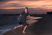 A young woman runs from encroaching surf.
