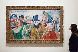 """© Licensed to London News Pictures. 25/10/2016. London, UK.  A staff member views """"The Intrigue, 1890"""" at the preview of Intrigue: James Ensor by Luc Tuymans.  Curated by fellow Belgian artist Luc Tuymans, this is the first exhibition of work by modernist artist James Ensor (1860-1949) to be held in the UK in twenty years and will run 29 October 2016 to 29 January 2017. Photo credit : Stephen Chung/LNP"""