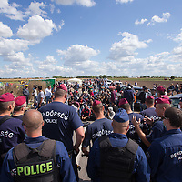 Line of police officers stands guard at a collection point of illegal migrants after some of the migrants tried to break out from police custody near Roszke (about 174 km South of capital city Budapest), Hungary on September 07, 2015. ATTILA VOLGYI