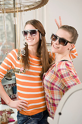 Young women trying sunglasses at fashion store, smiling