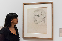 """© Licensed to London News Pictures. 21/01/2020. LONDON, UK. A staff member views """"Self-portrait (Montrouge)"""", 1918, by Pablo Picasso at the preview of """"Picasso and Paper"""", an exhibition at the Royal Academy of Arts, which is the most comprehensive exhibition ever devoted to Pablo Picasso's imaginative and original uses of paper .  Over 300 works both on and with paper, are on display 25 January to 13 April 2020.  Photo credit: Stephen Chung/LNP"""